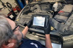 Mechanic working on a vehicle at Amtech Auto Care Inc. - image #2
