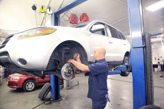 Mechanic working on a vehicle at Amtech Auto Care Inc. - image #8